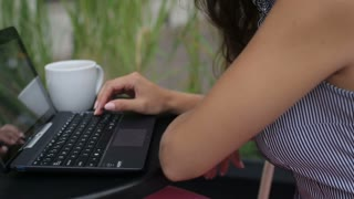 Upset woman received bad results on laptop and sitting in the street cafe