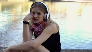 Very sad girl listening music by the river and looking to the camera