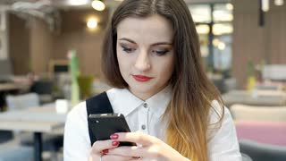 Absorbed businesswoman texting messages on smartphone in the cafe