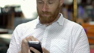 Absorbed man sitting in restaurant and browsing internet on smartphone, close up