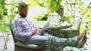 Absorbed man sitting in the garden and browsing internet on tablet