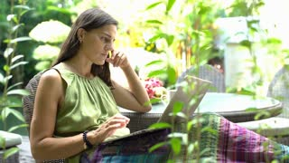 Absorbed woman sitting in the garden and using modern ultrabook, steadycam shot