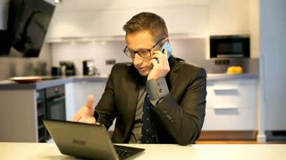 Angry businessman working on laptop and talking on cellphone in the kitchen
