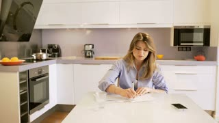 Angry woman destroying papers in the kitchen and throwing them
