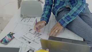 Architect sitting on the desk in the new flat and working on the project, steady