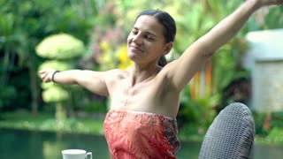 Attractive tanned woman relaxing in exotic place and stretching arms, steadycam