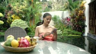 Attractive tanned woman sitting in exotic place and browsing internet on smartph