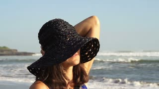 Attractive woman in straw hat smiling to the camera on the beach, steadycam shot