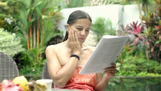 Attractive woman looks shocked while reading news in gazette, steadycam shot