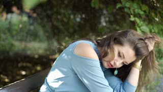 Attractive woman looks worried while thinking about something in the park, stead