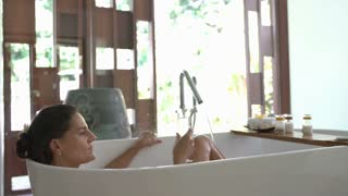 Attractive woman lying in the bath and drinking champagne