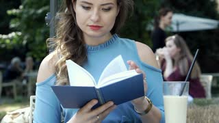 Attractive woman reading book in the outdoor cafe and smiling to the camera, ste