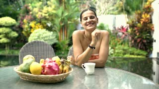 Attractive woman smiling to the camera and drinking coffee in exotic place, stea