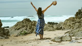 Beautiful woman feels free and happy while standing on the beach, steadycam shot