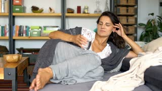 Beautiful woman in cosy clothes drinking water while lying on the couch