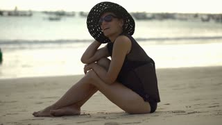 Beautiful woman in straw hat sitting next to the sea and relaxing, steadycam sho