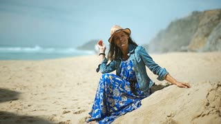 Beautiful woman sitting on the sandy beach and smiling to the camera