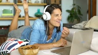 Beautiful woman watching video on notebook and eating snack while smiling to the