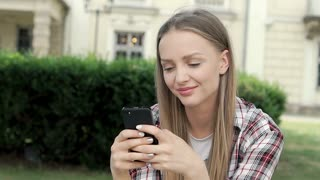Blonde girl in checked shirt texting messages on smartphone, steadycam shot