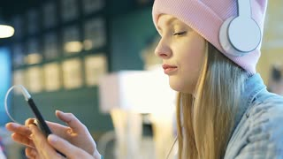 Blonde girl in pink beanie plays music on smartphone and listening it in the caf