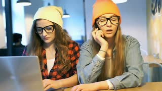 Blonde girl is quarrelling on cellphone while her friend is typing on notebook