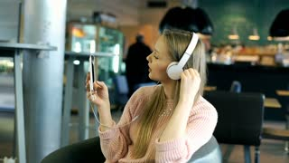 Blonde girl listening music and spinning on the chair while smiling to the camer