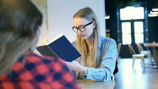 Blonde girl receives message while reading book in the cafe, steadycam shot