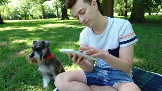 Boy checking tablet and receives bad news while sitting in the park with his dog
