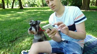Boy relaxing with his dog in the park and doing selfies on smartphone, steadycam