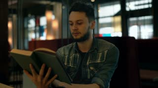 Boy with beard reading interesting book in the dark cafe and reading book