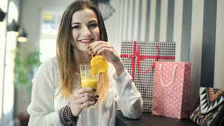 Brunette drinking fresh orange juice and smiling to the camera, steadycam shot