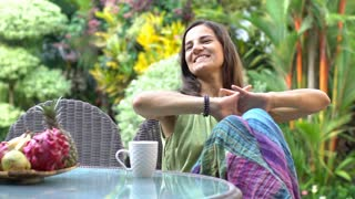 Brunette relaxing in her exotic garden and smiling to the camera, steadycam shot