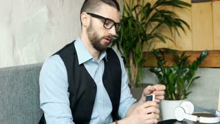 Businessman connects headphones to smartphone and starts listening music, steady