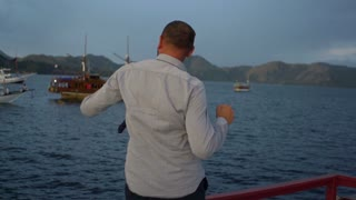 Businessman dancing next to the sea, steadycam shot, slow motion shot at 240fps
