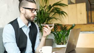 Businessman having a businesscall and working on notebook in the cafe, steadycam