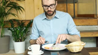 Businessman looks unhappy while eating spoiled food in the restaurant, steadycam