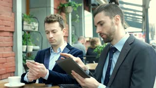 Businessman using disconnected screen from laptop and showing something on it to