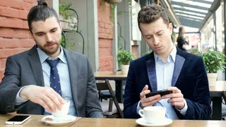 Businessmen talking with each other and looking on smartphone, steadycam shot