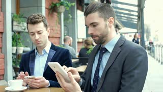 Businessmen talking with each other while using electronics, steadycam shot