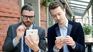 Businessmen using electronics and showing something to each other in the cafe, s