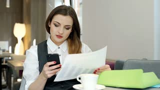 Businesswoman comparing data on papers with these on smartphone