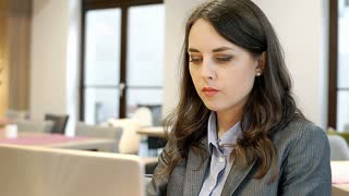 Businesswoman looks dissatisfied while working on laptop in the cafe