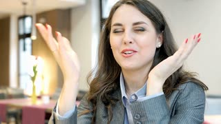 Businesswoman looks excited while talking to someone in the cafe