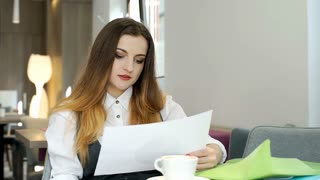 Businesswoman looks worried while checking documents in the cafe