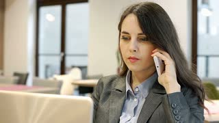Businesswoman looks worried while speaking on cellphone and checking something o