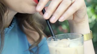 Close up of woman drinking iced coffee, steadycam shot