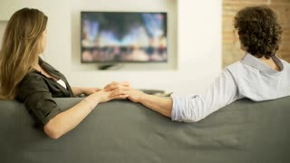 Couple holding each other hands while sitting on the sofa and watching tv