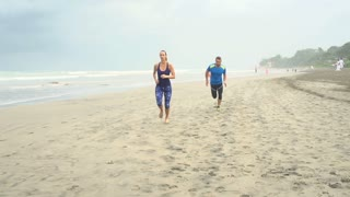 Couple jogging on the beach together, steadycam shot, slow motion shot at 240fps