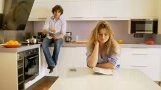 Couple read some publications in the kitchen and woman smiling to the camera