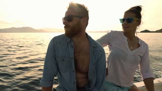 Couple sitting on a yacht and looking on something, slow motion shot at 240fps,